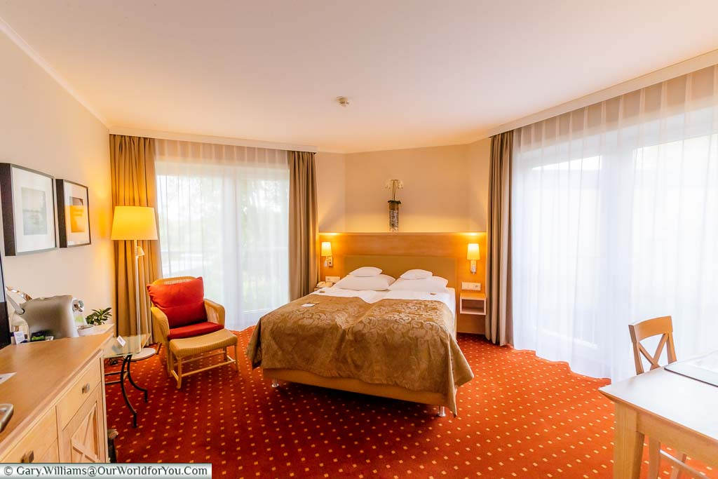Our spacious, brightly lit, bedroom a the Best Western Premier Alsterkrug Hotel featuring a large double bed with two individual quilts, and separate working area.