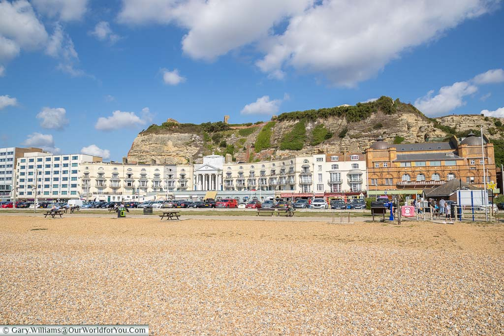 The view from the cobbled beach back to Pelham Crescent with Hastings Castle ruins above