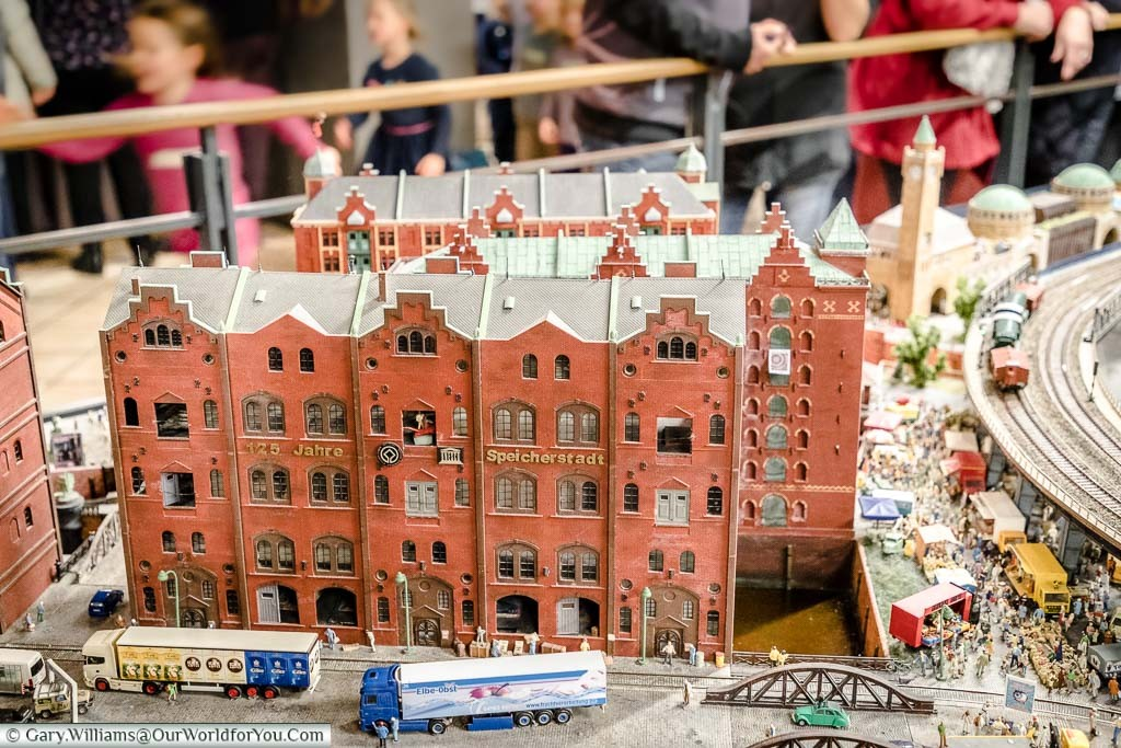 A model scene from Miniature Wonderland depicting the red brick warehouses of the Speicherstadt district with train tracks running alongside in front of the old Harbour building.