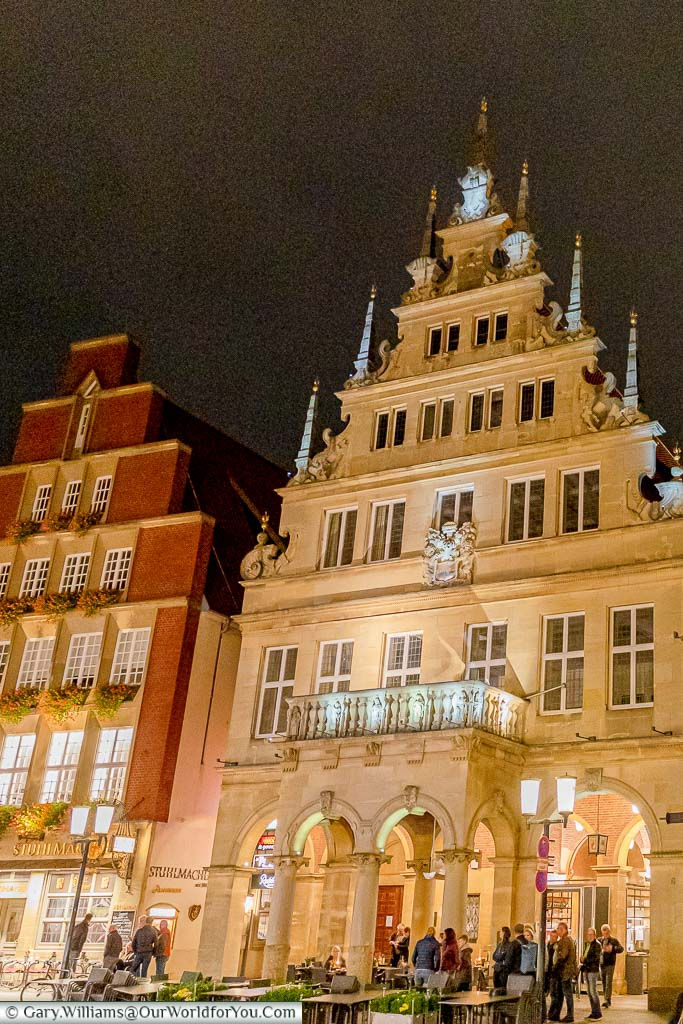 The floodlit Stadtweinhaus at night where a few folks have gathered at the bar that occupies the lower level of this historic building.