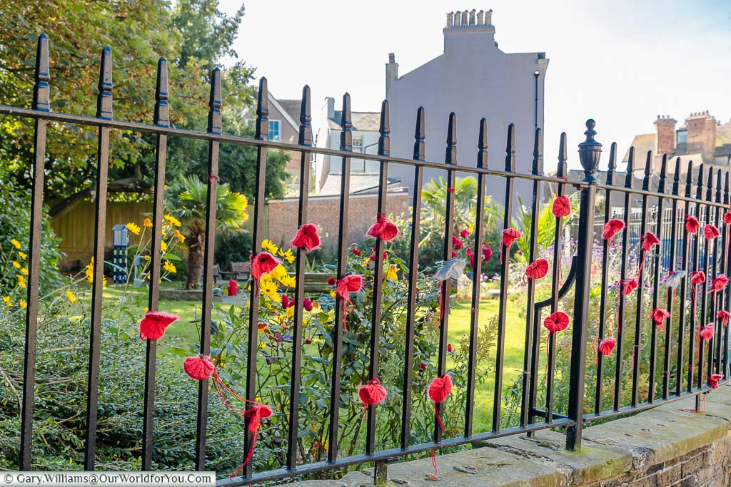 Knitted poppies attached to the iron railings of the Bayle Pond in Folkestone, Kent