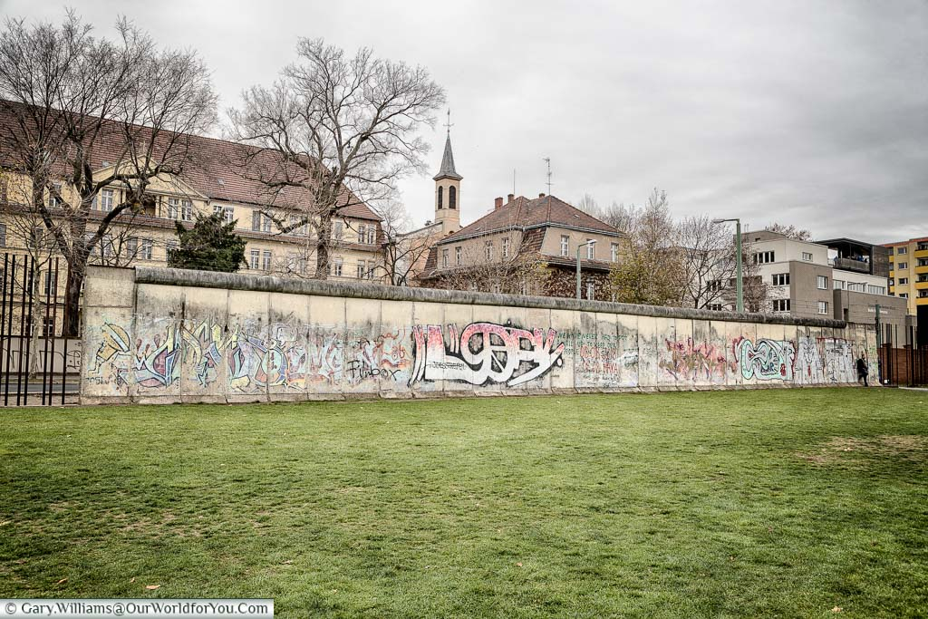 The graffitied Berlin Wall in front of a section of grass that made up the no-man's-land area in front of the wall on a grey December day.