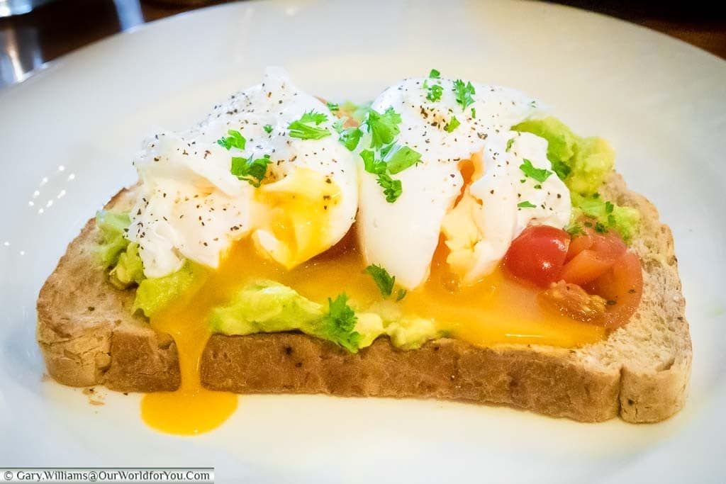 Two split poached eggs on chilli avocado on wholegrain toast sprinkled with bright green parsley.