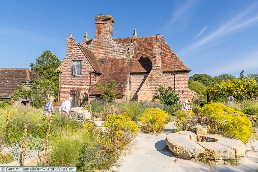 A view of the Elizabethan Priest's House with the planting of the Mediterranean themed Delos Garden at Sissinghurst Castle Garden
