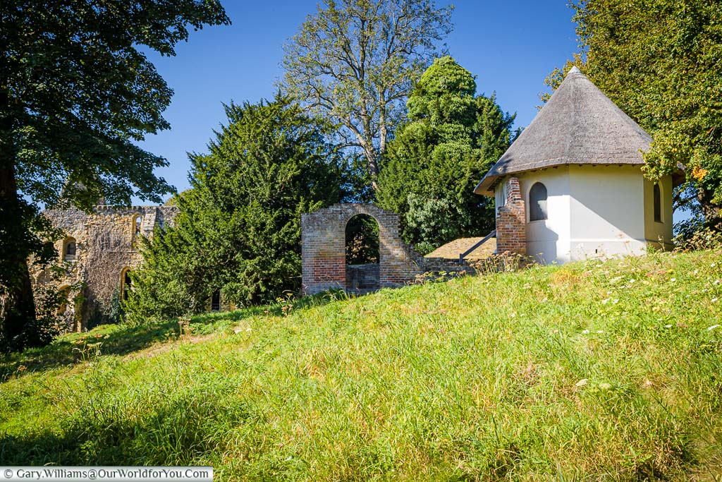 A view of a meadow in front of the small octagonal thatched Victorian Dairy building.
