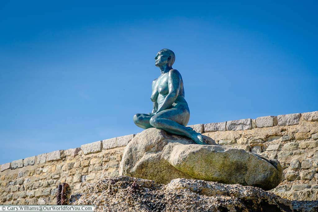 Looking up at the life-sized bronze figure of the Folkestone Mermaid perched on rocks at the edge of Folkestone's Sunny Sands beach