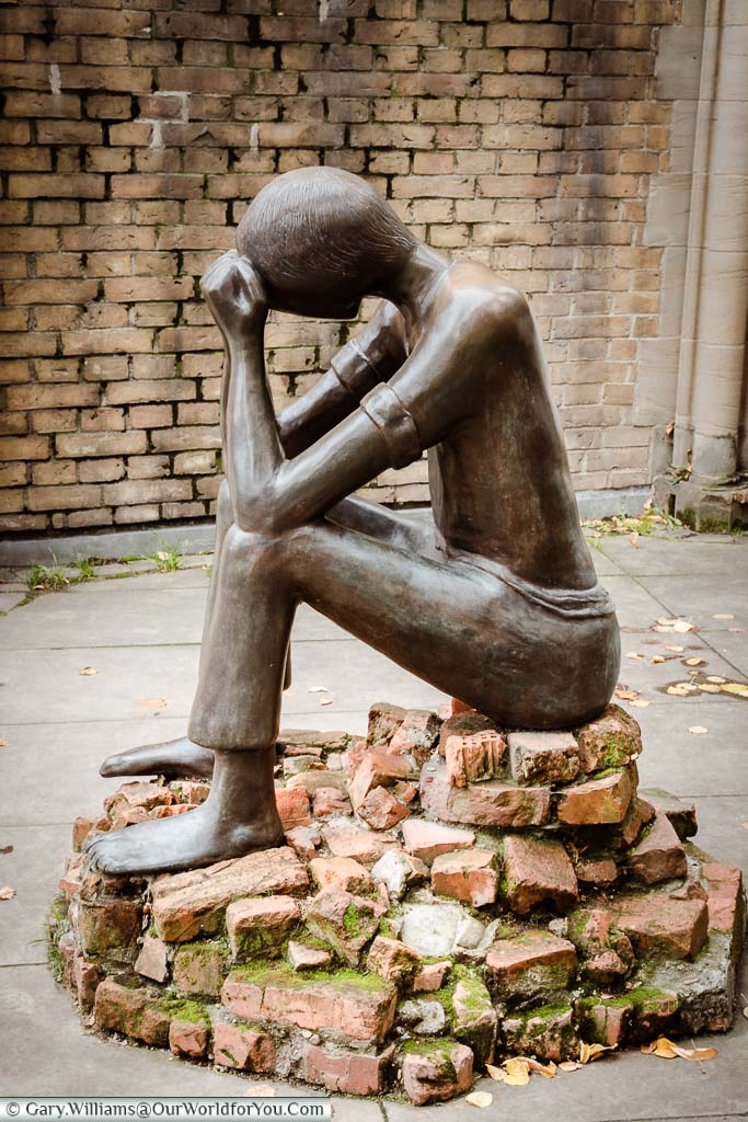 The Ordeal, by Edith Breckwoldt. A bronze statue of a barefooted man sitting on a pile of bricks with his head in his hands.