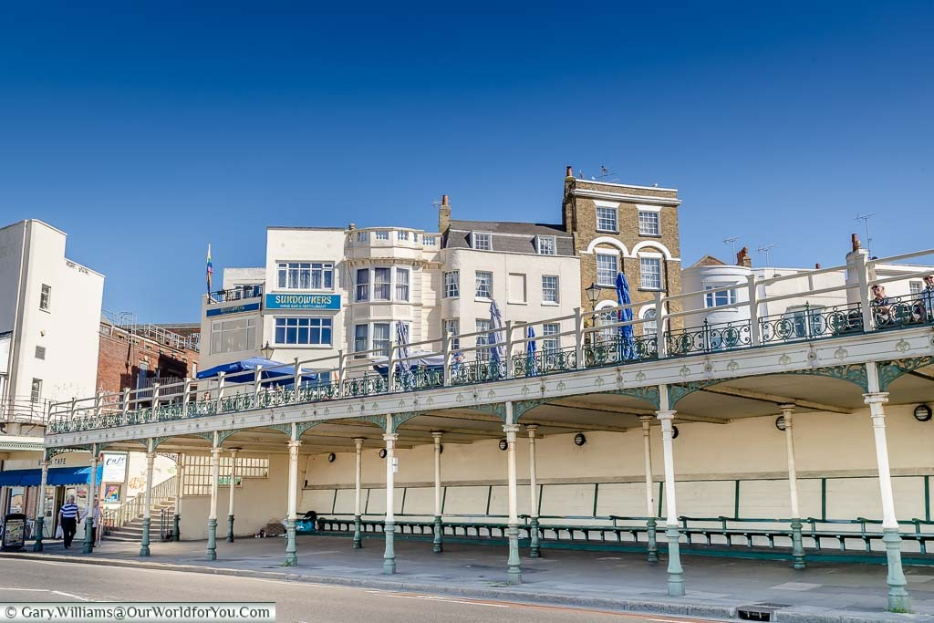 A row of benches under a Victorian shelter on The Parade in Margate Kent