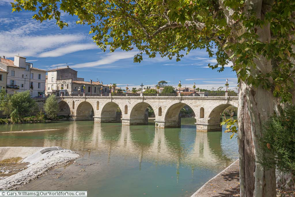 The old stone Pont Du Romain, Roman bridge, across the River Vidourle in Sommières, France