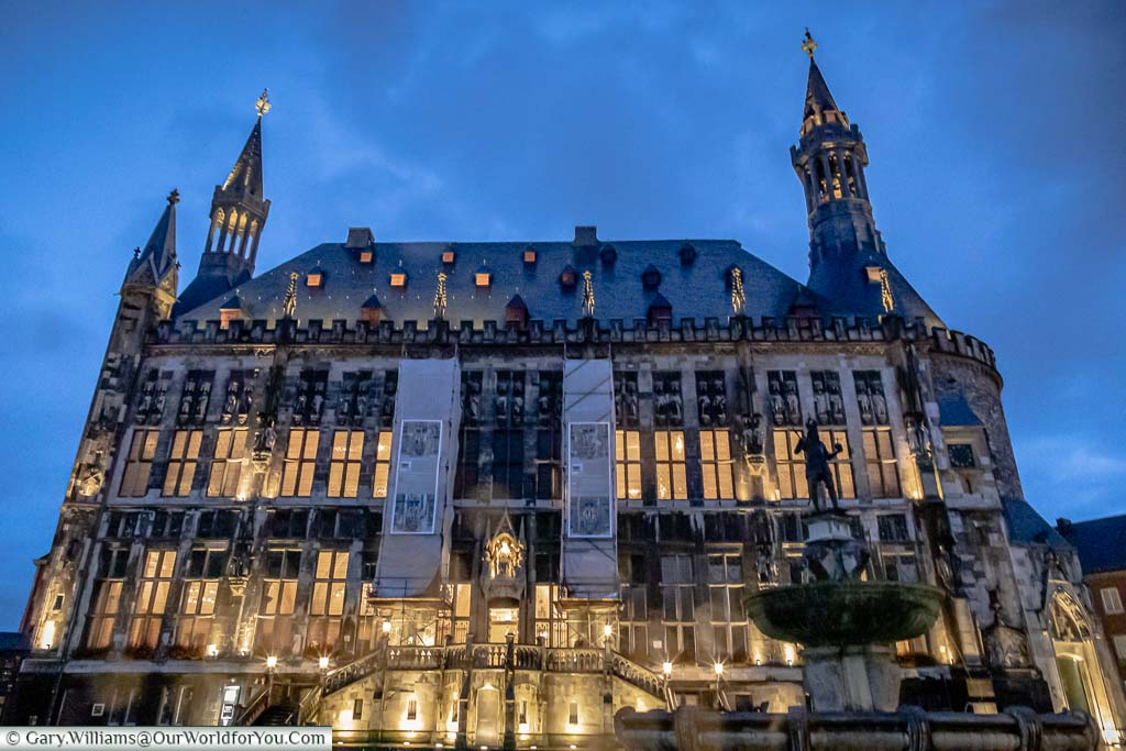 The front of the Rathaus at dusk, with the statue of Charlemagne on the right.