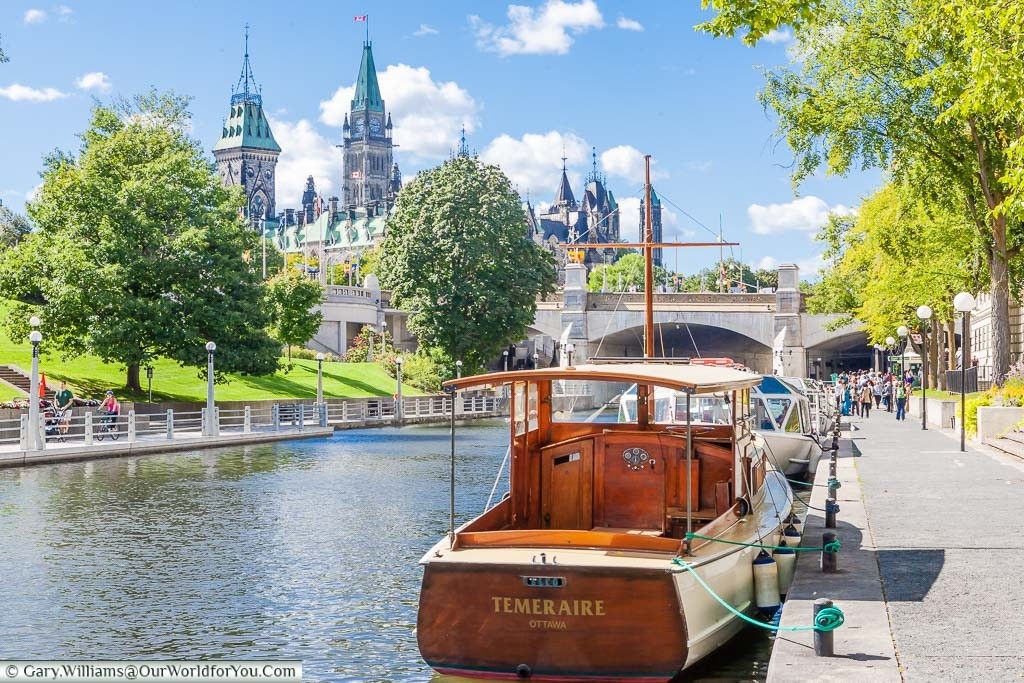 Pleasure boats moored up on the Rideau Canal in Ottawa with the Parliament of Canada in the background.