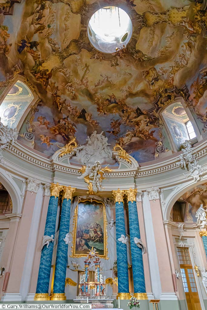 The elegant baroque decorated interior of the Clemenskirche with blue pillars capped with gold detailing against pale pinks & greens.