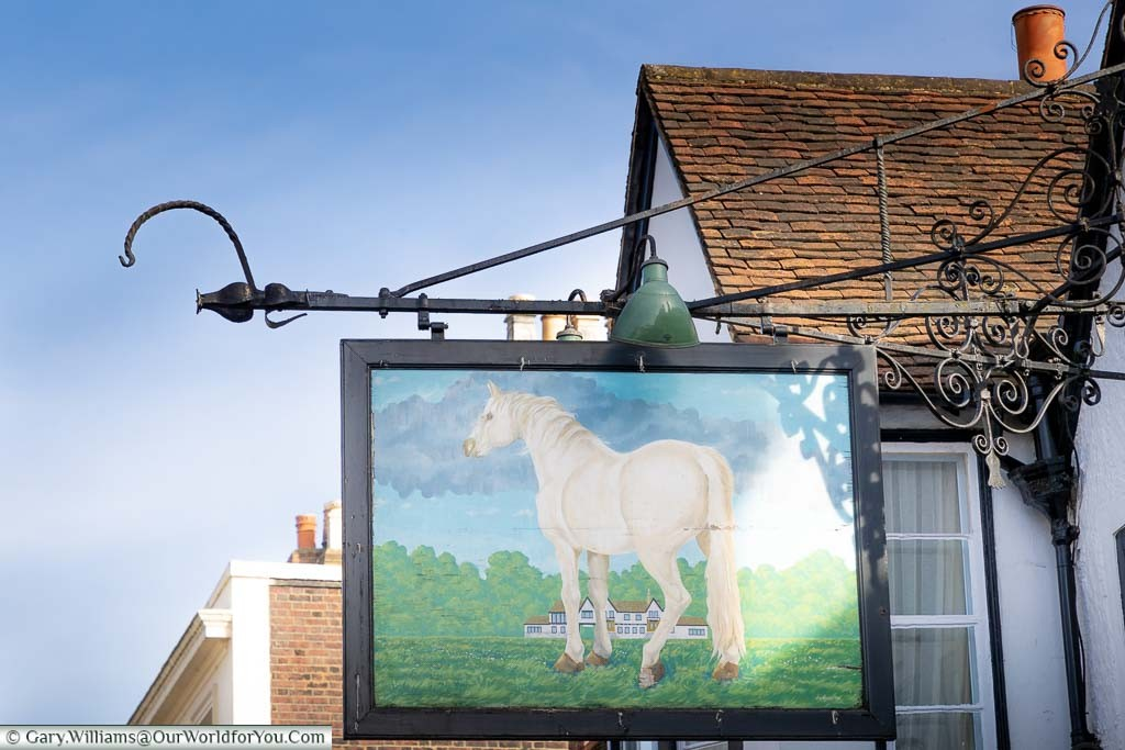 A traditional hanging sign above the White Horse hotel featuring a white horse in a field in front of the former coaching inn.