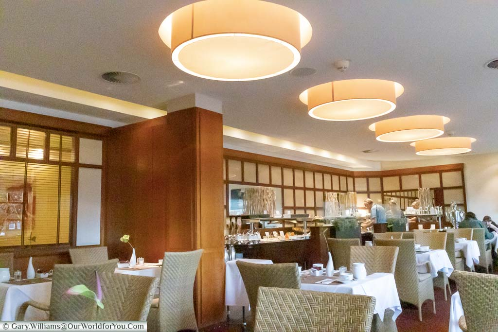 The spacious dining area of the breakfast lounge at the Best Western Premier Alsterkrug Hotel, Hamburg. A wide selection of foods and drinks are available from the continental breakfast bar.