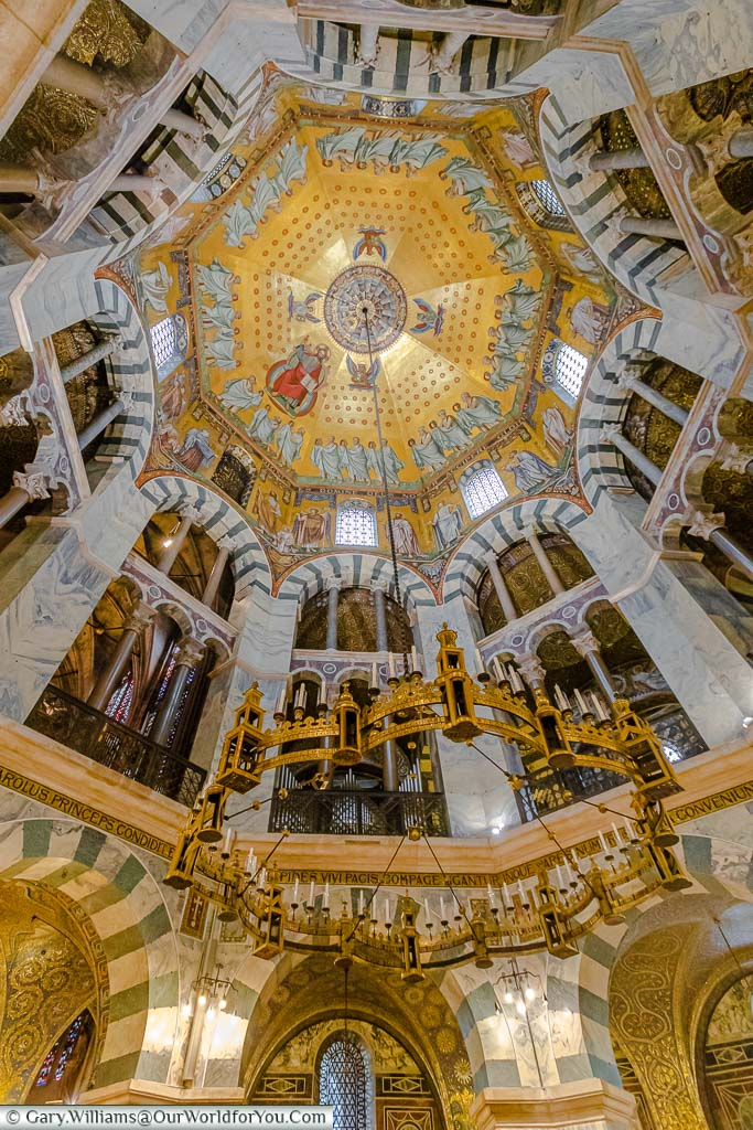 A closer look at the Barbarossa Chandelier attached to the centre dome of Aachen's Dom. From this view, you can see the detail of the arches and the ornate decoration of the dome itself.