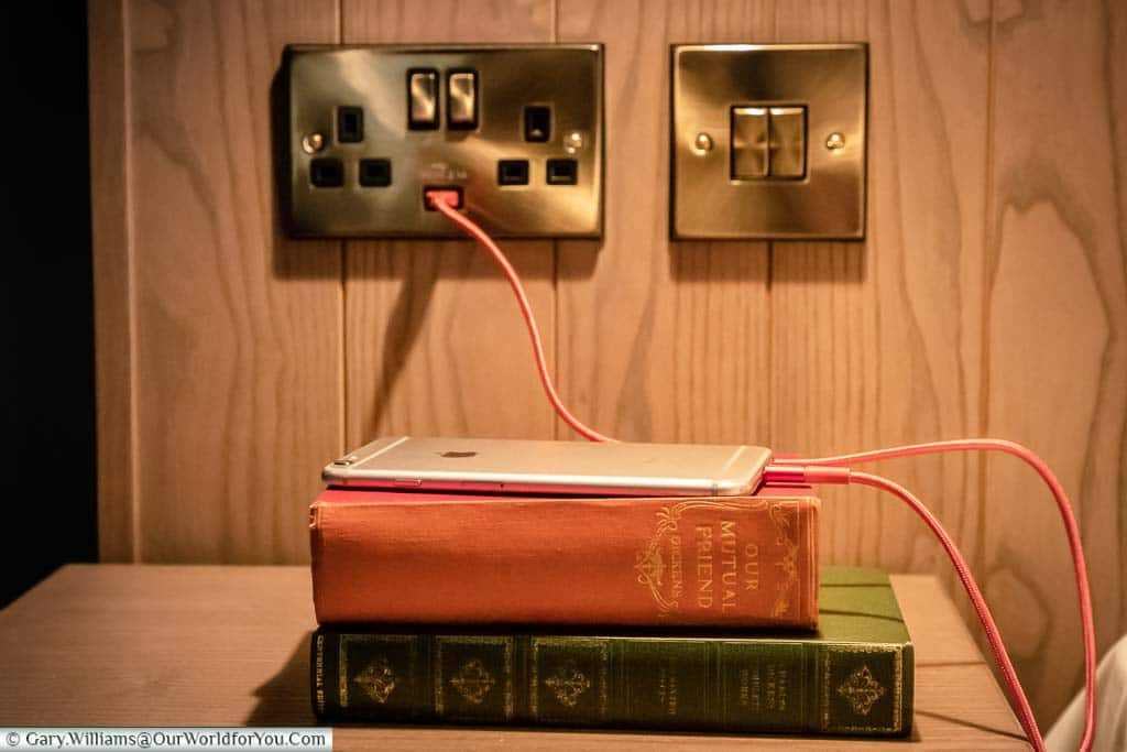 An iPhone, resting on couple of Dickens novels, charging directly off the USB socket included in the mains power socket.