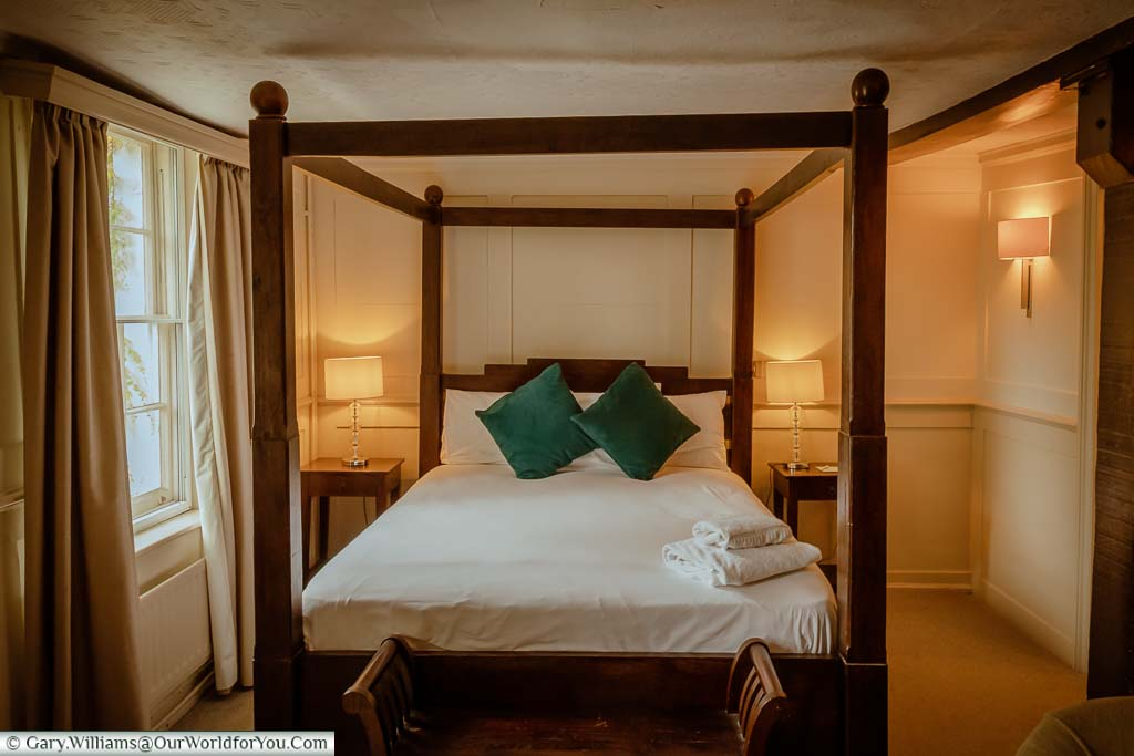 The solid wooden four-poster bed in our room
