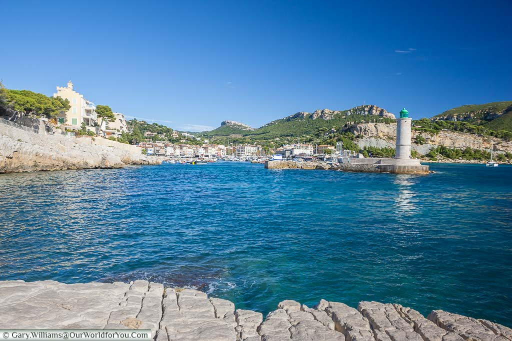 The entrance to the harbour at Cassis protected by a lighthouse, with the provencal town, in the background.