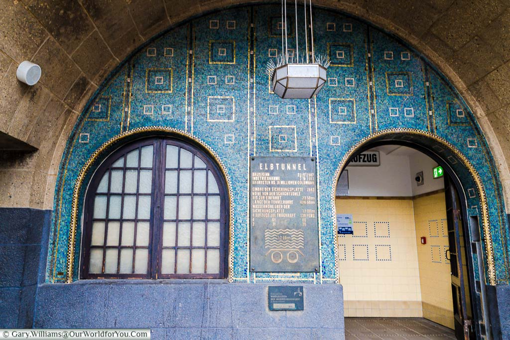 The art deco pedestrian entrance to the old Elbe tunnel with a brass plaque detailing facts about the tunnel.