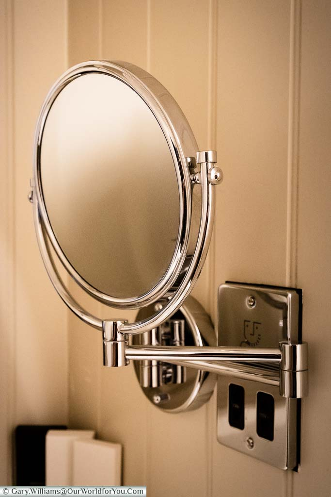 A highly polished chrome, wall-mounted, saving mirror in our bathroom in the White Horse hotel in Dorking