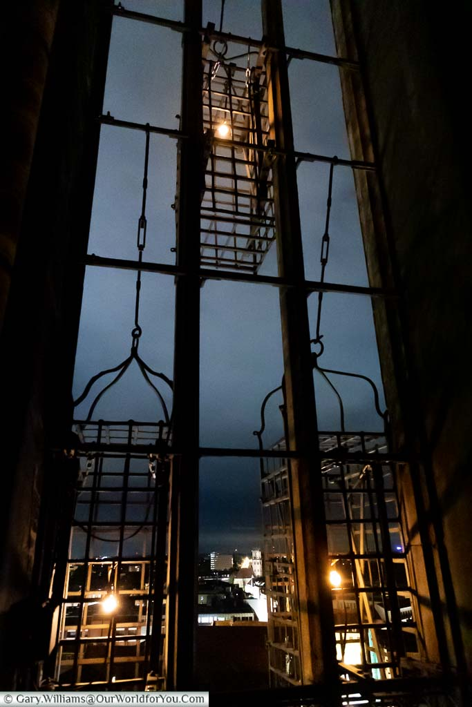 Inside the bell tower of St. Lamberti Church at night looking out at the 3 Anabaptist cages, illuminated with a single light bulb.