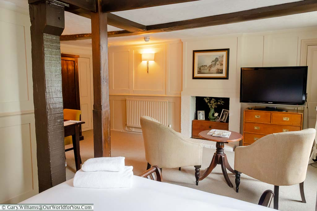 The view of our spacious room, the Trafalgar, from the four-poster bed, across the lounge area with two comfortable chairs, and occasional table, the TV and the old fireplace.