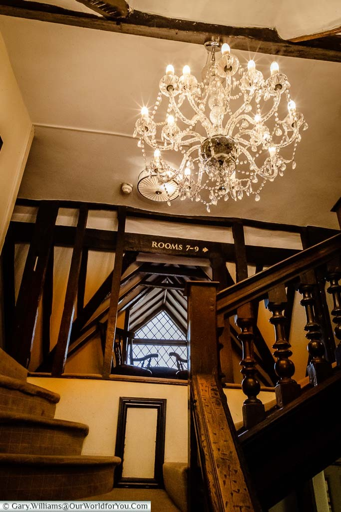 Looking up the stairs of the original building of the Talbot Inn with its heavy beams, dark wood, brightened with a beautiful chandelier.