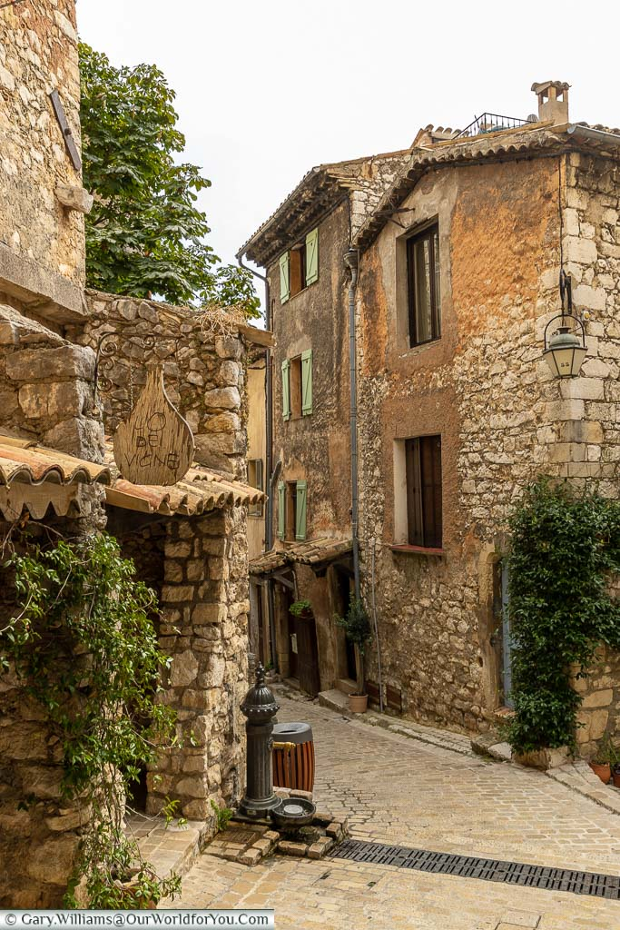 A narrow cobbled lane between rough stone provencal buildings in Tourrettes sur Loup
