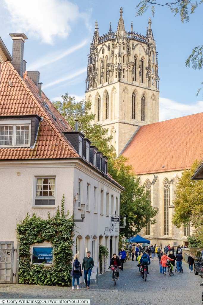 """A view down a cobbled lane over the river Aa to the church named Überwasserkirche which translate as """"church over the water"""". The sandstone gothic tower is flat, the spire was removed during the Anabaptist rebellion."""