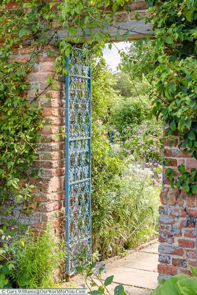 A latticed wrought iron gate in the walled gardens of Sissinghurst Castle Garden, Kent, England