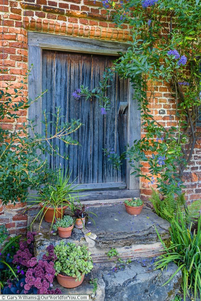 Potted plants around a wooden door in the red brickwork of Sissinghurst Castle, Sissinghurst Castle Garden, Kent, England