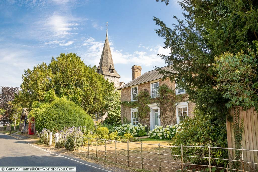 Charming cottages, with the spire of Saint Peter and Paul Church in the background, in Newnham, Kent