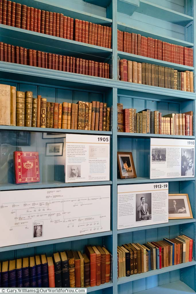 Rows of books on teal blue bookshelves in the study of Eddy Sackville-West in the gatehouse tower of Knole house