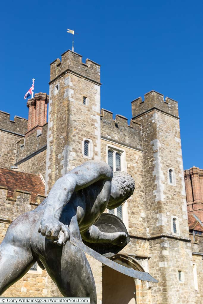 A bronze sculpture of a gladiator in a fighting pose in front of one of the towers of Knole House.