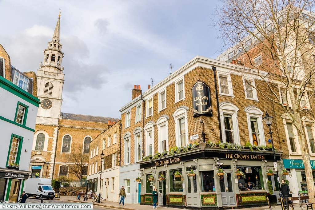 A street scene from Clerkenwell, East London, featuring the Crown Tavern and church in the background.