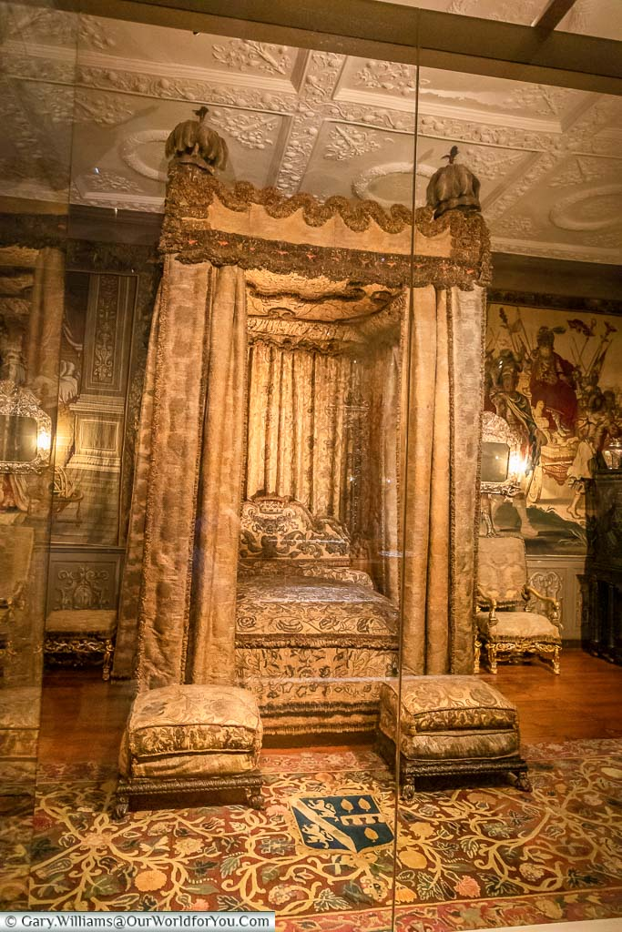 An ornate four-poster bed, with golden drapes, in the King's Bedroom within Knole House