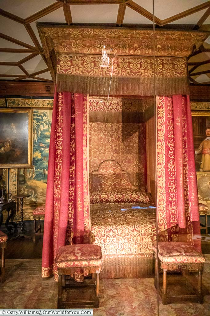 The 17th Century four-poster bed in the Spangle Bedroom with heavy red & gold drapes on each corner