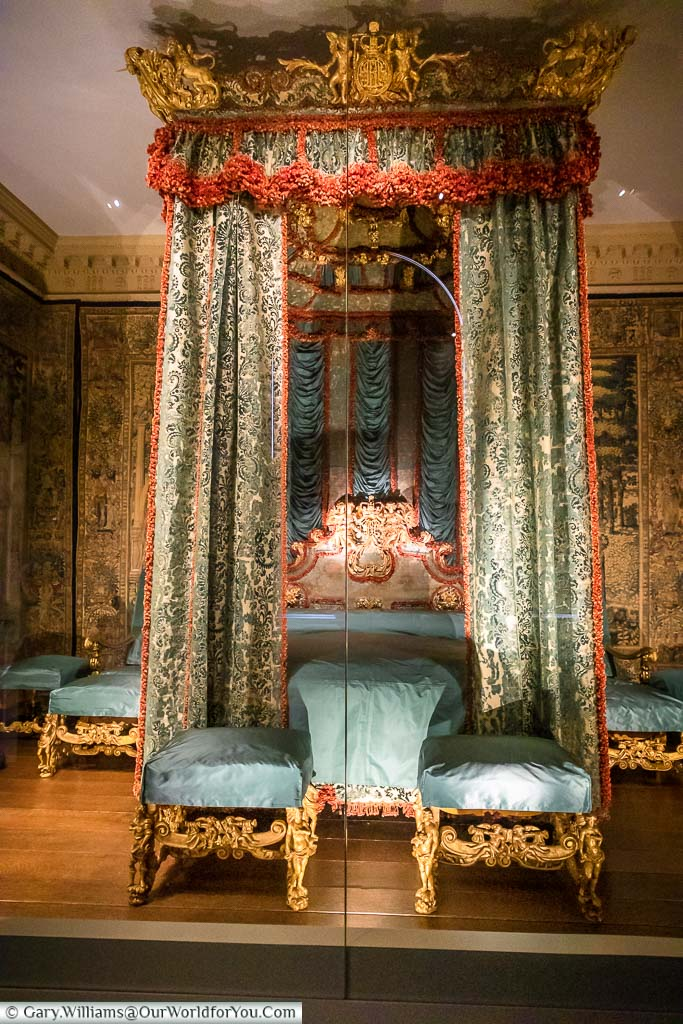 Green and red drapes ordain an ornate four-poster bed in the Venetian Bedroom within Knole House