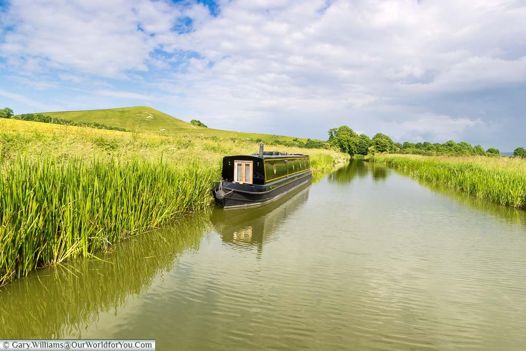 A lone narrowboat moored on the banks of the Kennet & Avon canal under a blue sky
