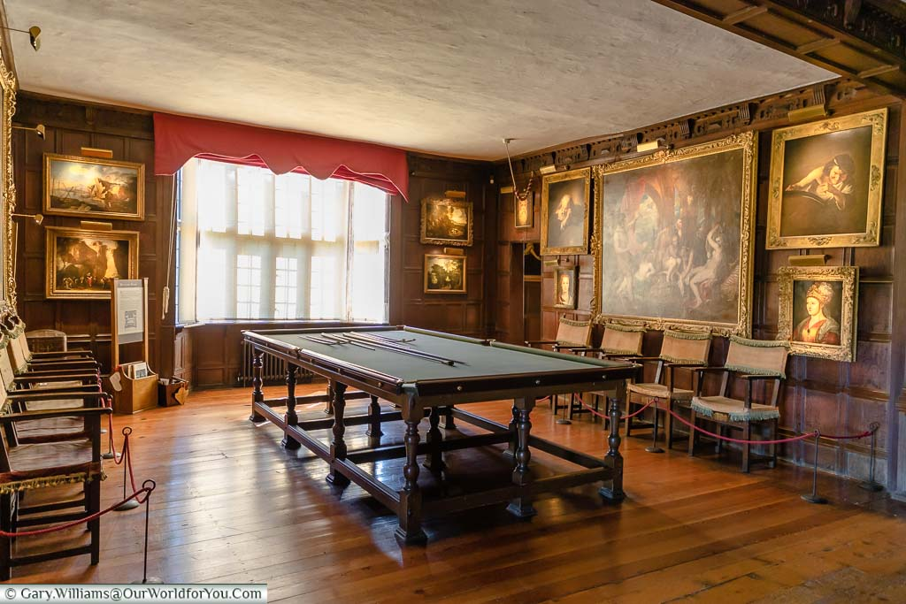 The oak-panelled billiard room decorated with portraits in Knole house