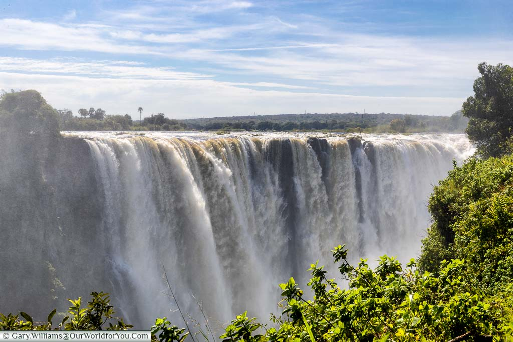 A section of Victoria Falls main waterfall taken in mid-April during the high water season. Despite the blue skies you're guaranteed to get wet from the mist generated by the falls.